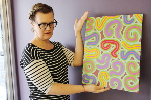 Muffy McKay shows off the Aaron Hagan painting to be raffled off during ArtsDays, Sept. 23-Oct. 1. Photo by Richard Amery