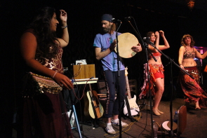 Pardip Athwal, Bocephus King and several local belly dancers perform together. Photo by Richard Amery