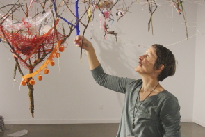 Annie Martin examines one of her nests in her exhibit flotilla at CASA. Photo by Richard Amery