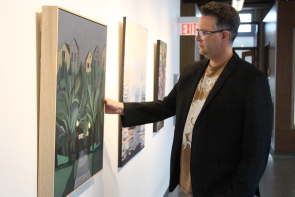 Darcy Logan examines one of the paintings in Casa's new Summer Salon exhibit. Photo by Richard Amery