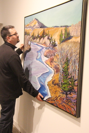 Darcy Logan adjusts a painting in the Castle River & Porcupine Hills exhibit before the opening reception tonight. Photo by Richard Amery