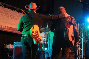 Dave Alvin and Phil Alvin celebrate brotherhood while watching a drum solo during their set at the Wide Skies music Festival, July 27. Photo by Richard Amery