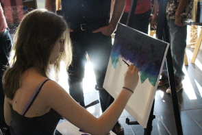 Kaitlyn Villenuve paints at the Helping Families fundraiser, May 27. Photo by Richard Amery