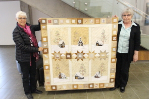 Trudy Walker and Teresa Petriw show Petriw's quilt incorporating her grandmother's doilies, which will be on display at at the Lethbridge Festival of Quilts, June 2 and 3 in the Lethbridge College Val Matteotti gym. Photo by Richard Amery.
